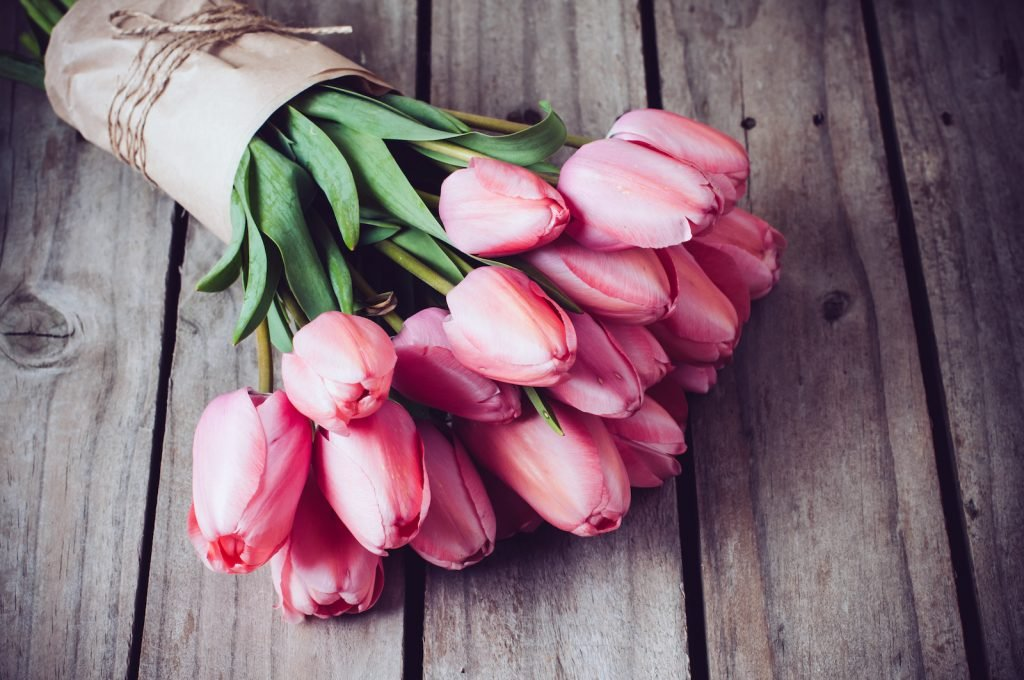 Bouquet of pink tulips lying on a rustic wooden table