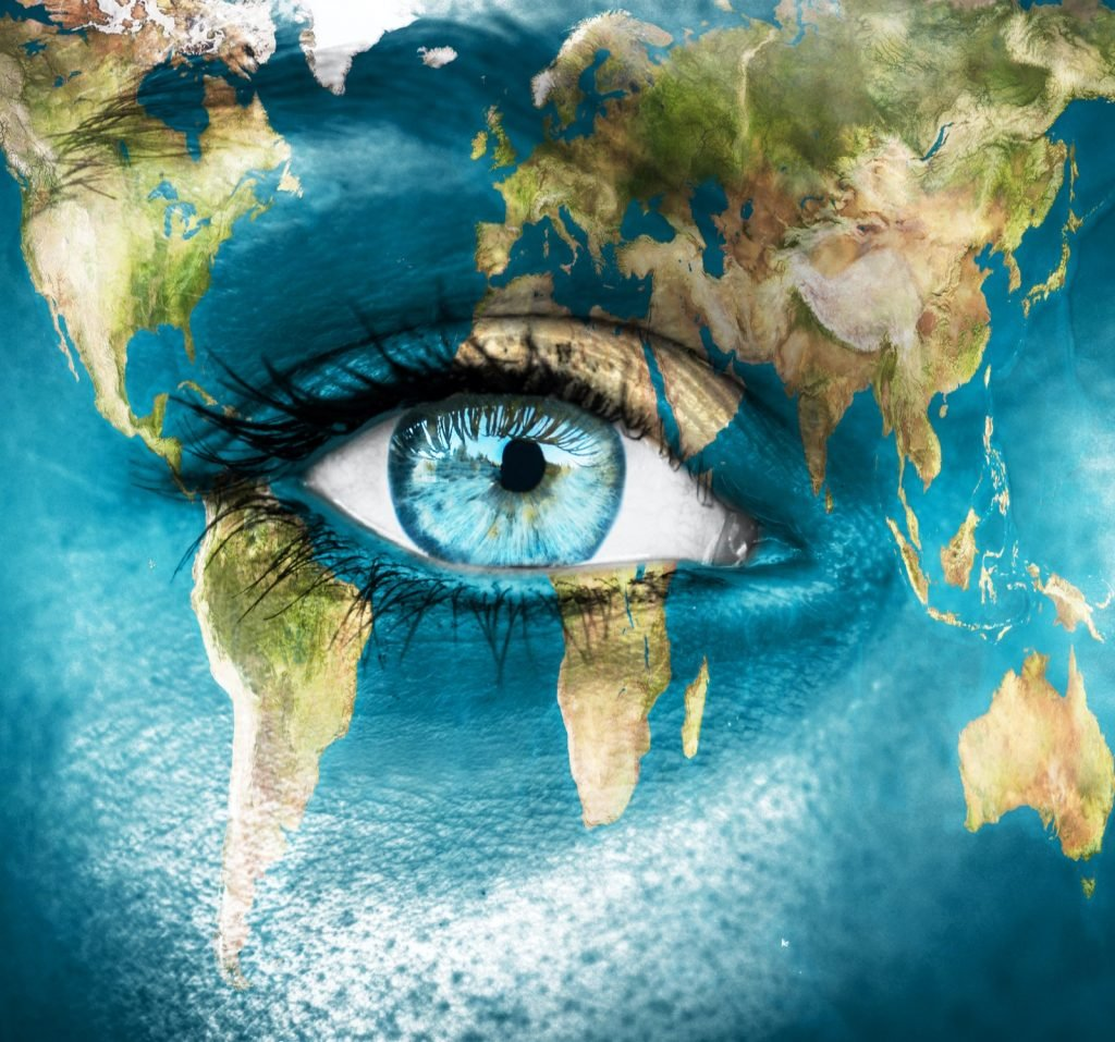 Human world perception concept with planet Earth painted on a woman's face surrounding her blue eye