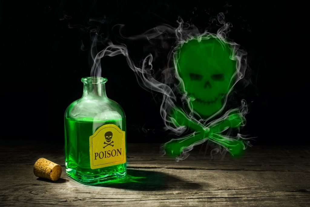 Green color liquid in poison glass vial with smoke and skull