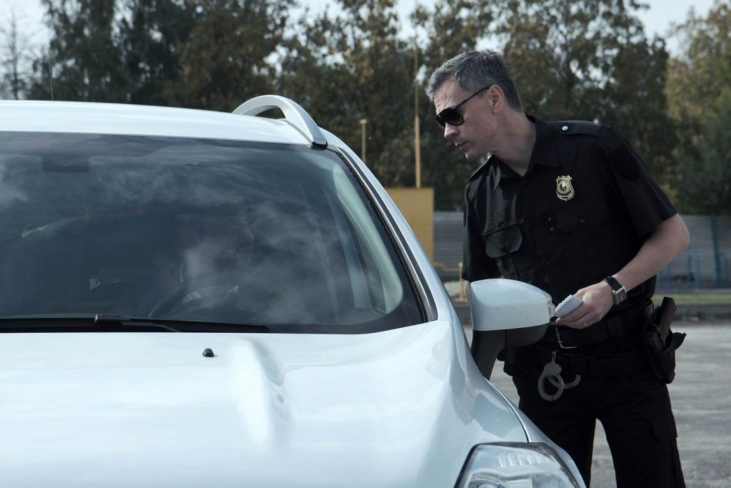 Police officer stopping driver of a white car and questioning him through the open window
