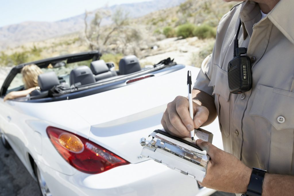 Police officer writing a speeding ticket to woman in convertible car