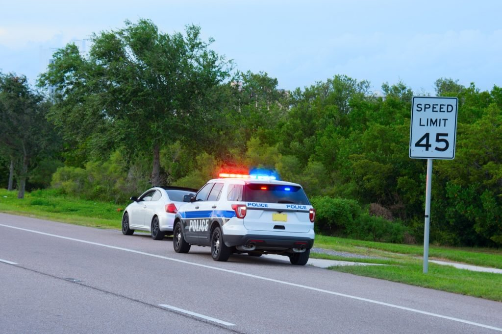 Police truck with flashing red and blue lights has pulled over a white car for speeding