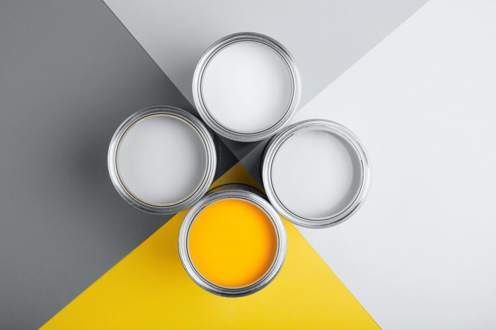 Popular colors of the year 2021 with four open cans of paint in gray, yellow, and white