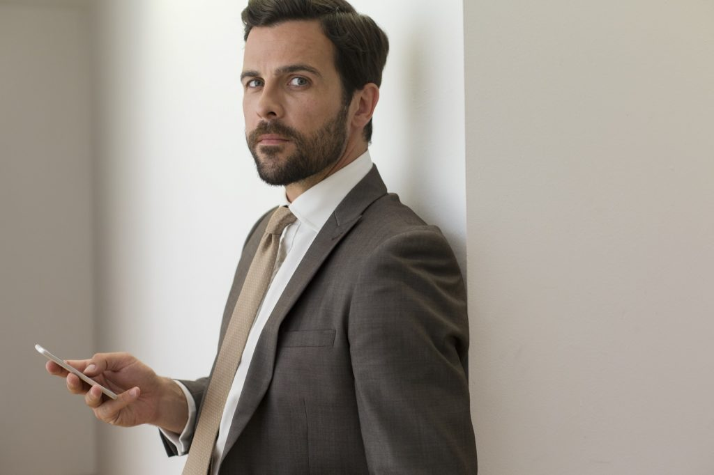 Portrait of corporate businessman with smartphone wearing brown suit