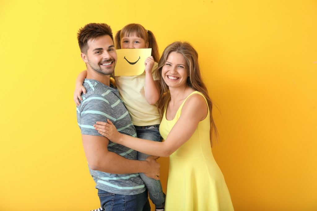 Portrait of happy family with drawn smile on sheet of paper against a yellow colored background