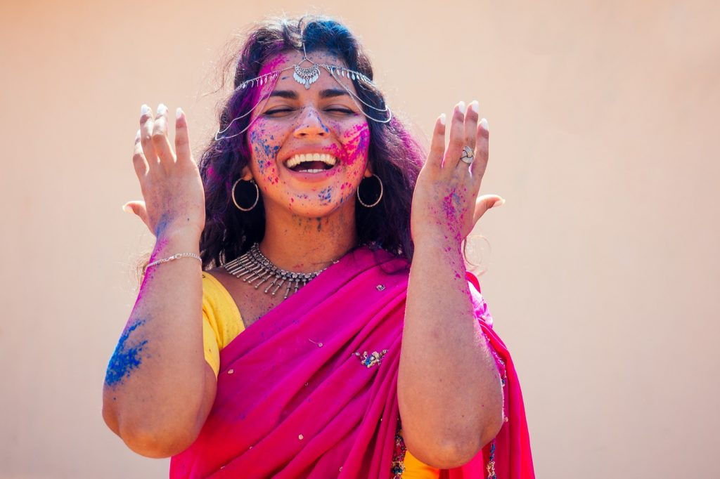 Portrait of happy Indian woman in dress covered with colored powder at Holi festival of colors