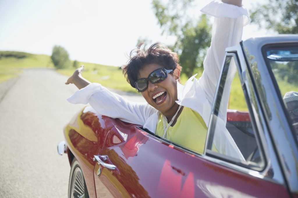 Portrait of excited middle-aged woman in red convertible car
