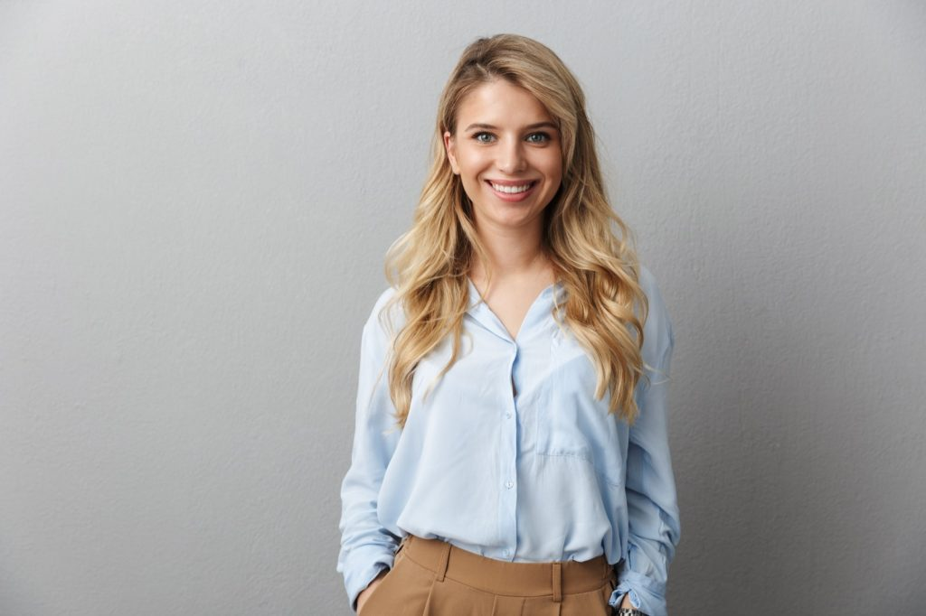 Portrait photo of blond woman with long curly hair smiling and standing with hands in her pockets isolated over grey background