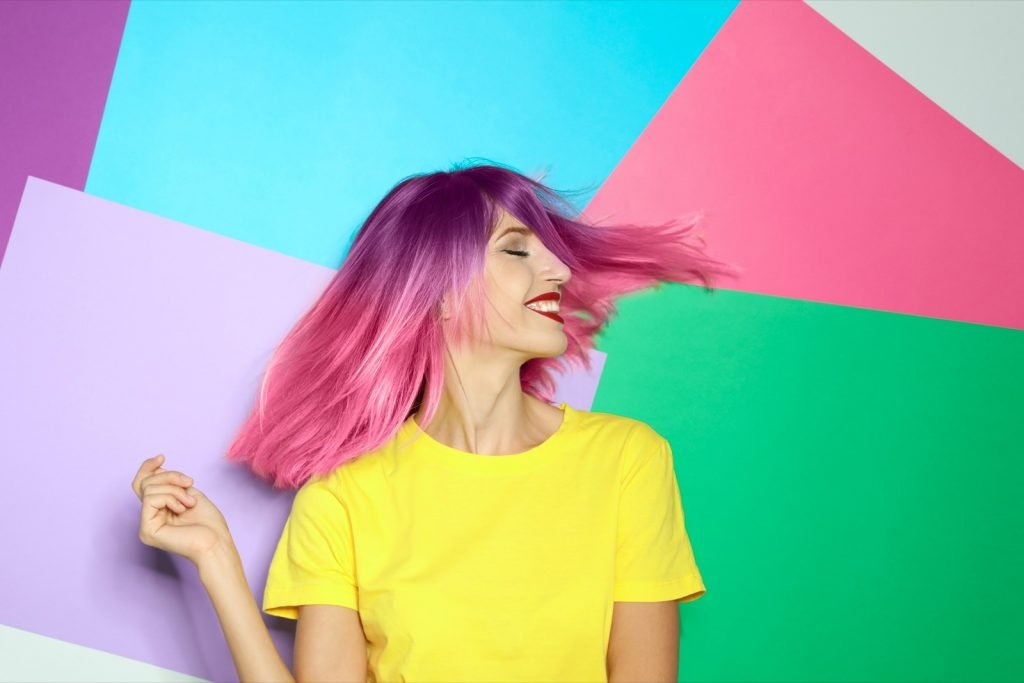 Portrait of smiling woman with trendy dyed hair on colorful background