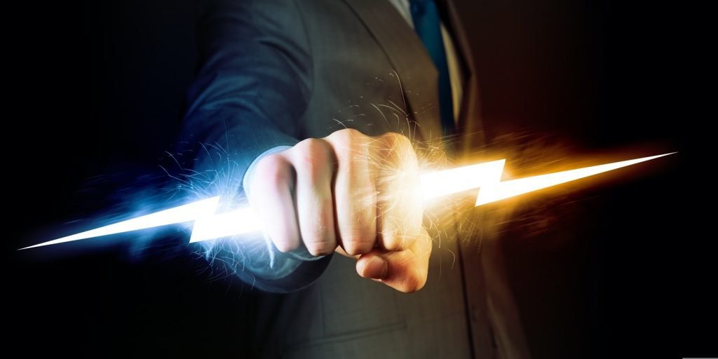 Man in black suit holding power in hand symbolizing control