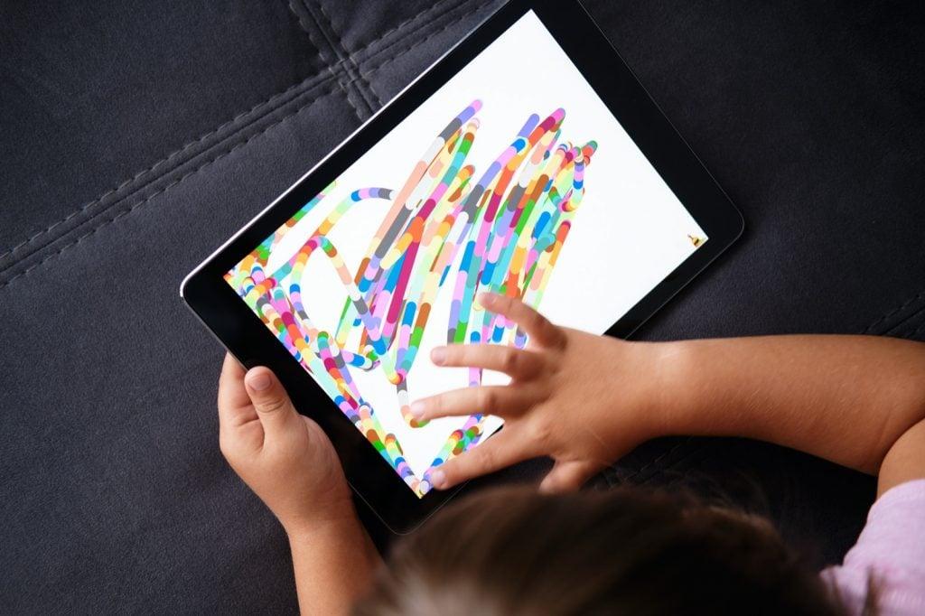 Preschool girl drawing on tablet in coloring app