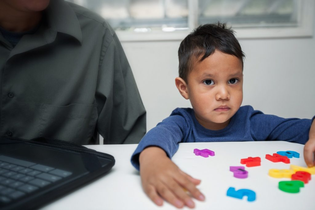 A preschooler is learning about colors at home using colored numbers