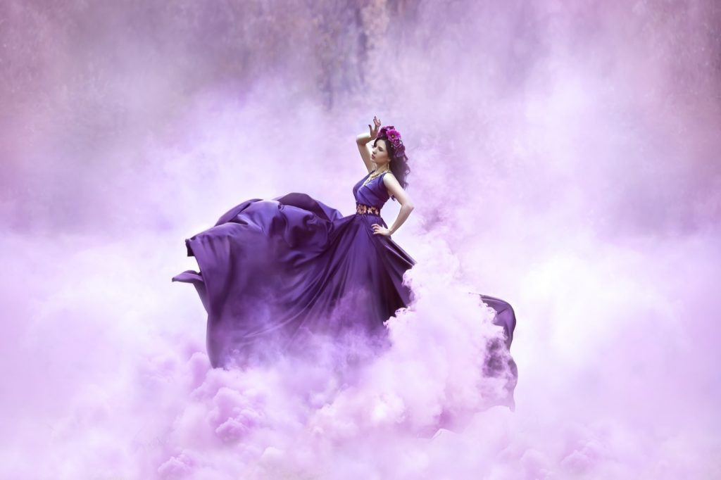 Princess in a royal luxury purple colored dress swirling in smoke