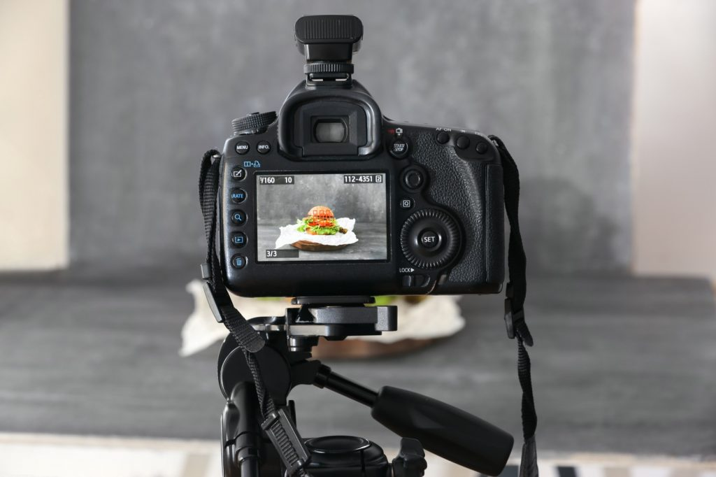 Professional camera on tripod photographing food on grey backdrop color