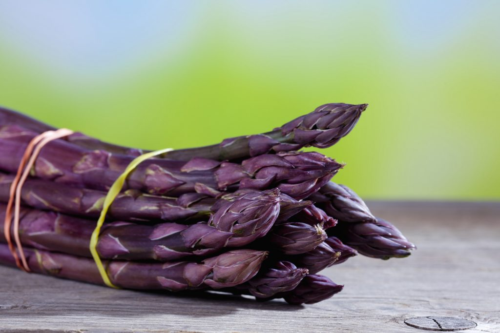 Closeup of a bundle of purple asparagus lying on a wooden table