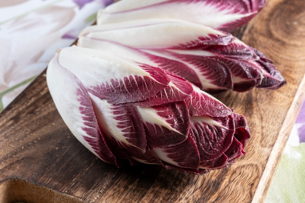 Close up of purple Belgian endive on a wooden chopping board