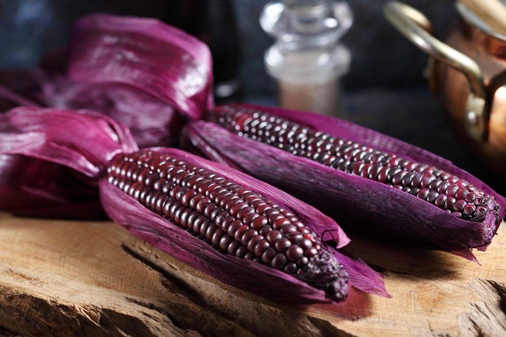Two purple corn cobs on a rustic wooden board