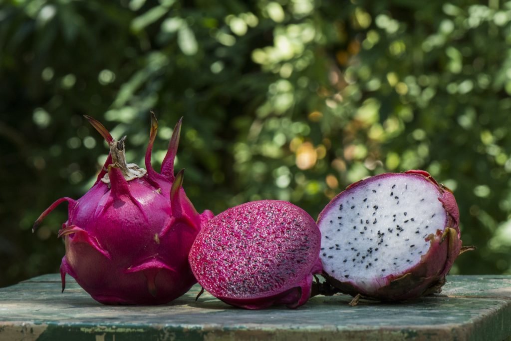 Two half of a purple and white flesh dragonfruit lies beside a whole dragonfruit on an rustic wooden table with green blurred background