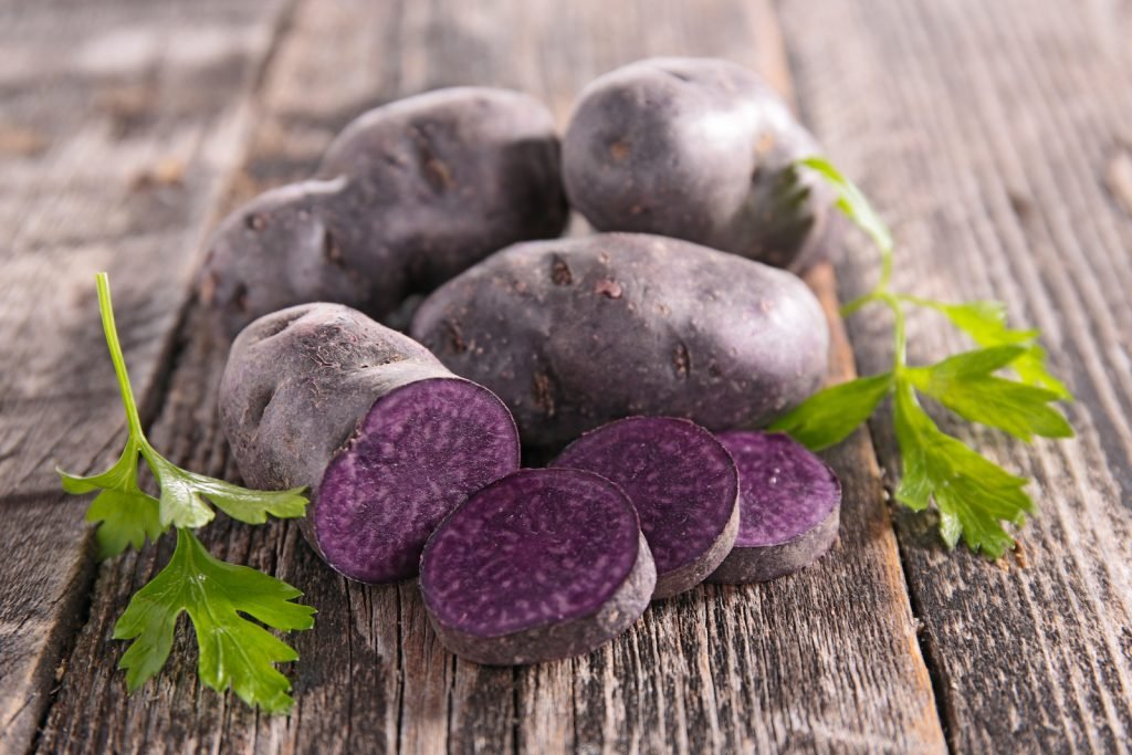 Purple raw potatoes  three whole and one in slices on a rustic wooden table