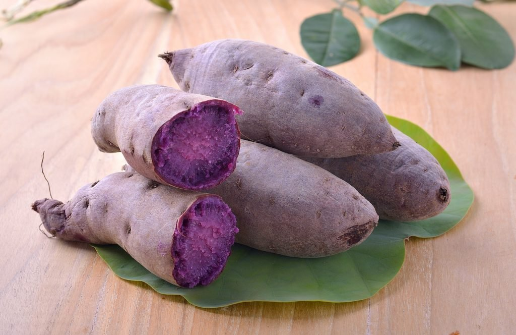 Purple yam also known as Ube lies in a stack on a big green leaf on a wooden table