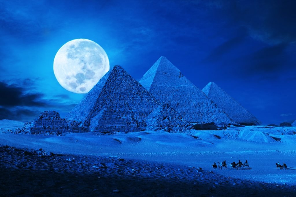 Pyramids in Egypt in a blue color lit up by the moonlight