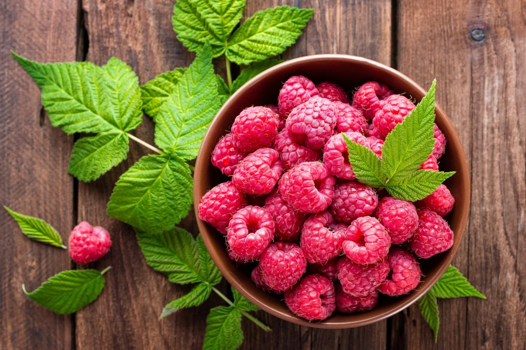 Top view of fresh raspberries with green leaves in a bowl standing on a rustic wooden table