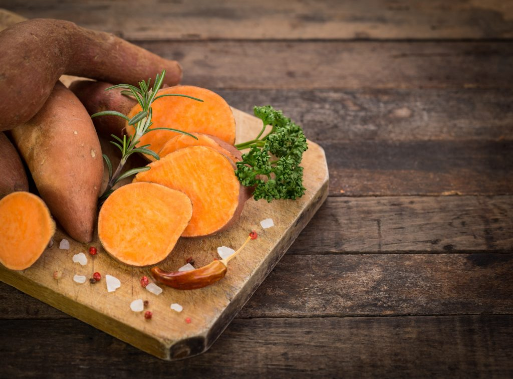 Raw sweet potatoes whole and sliced lying on a wooden chopping board on a rustic wooden table