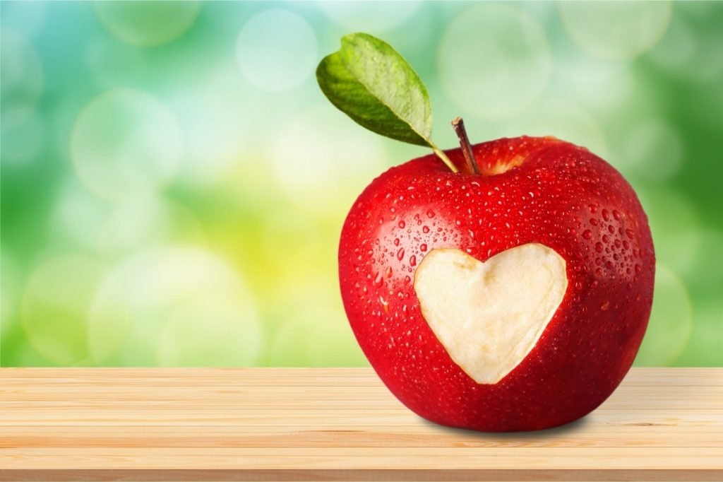 Red apple with a heart shaped on a green natural colored background