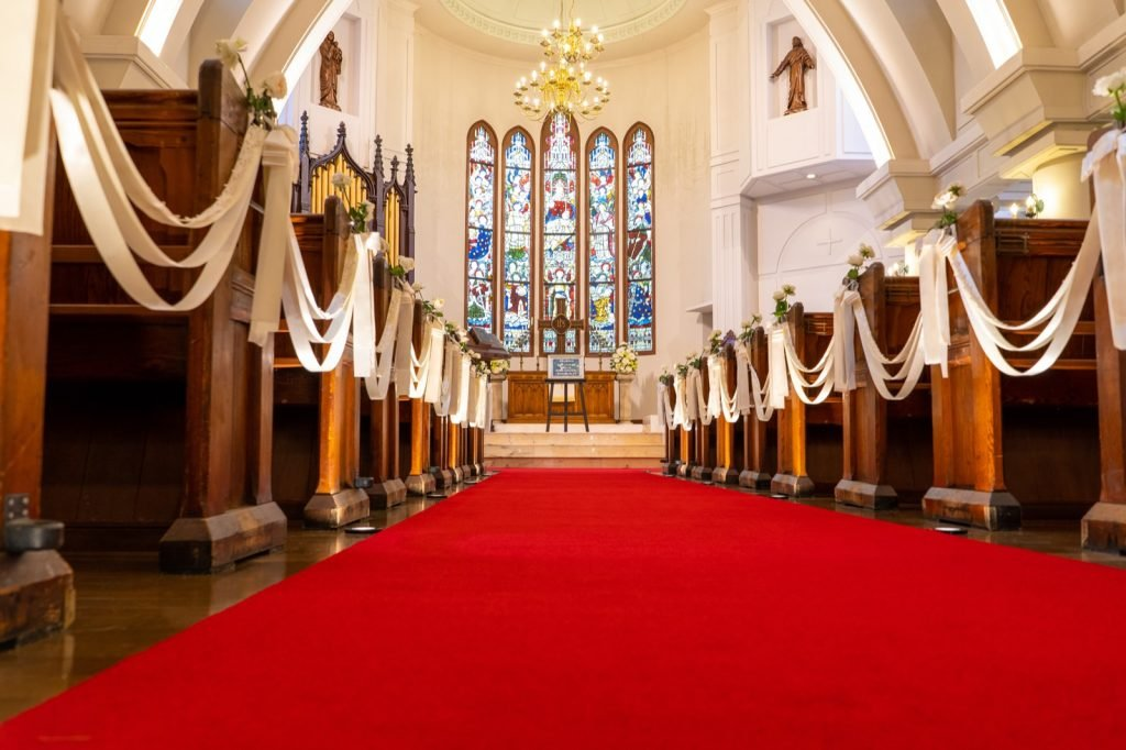 Red carpeted church aisle between pews