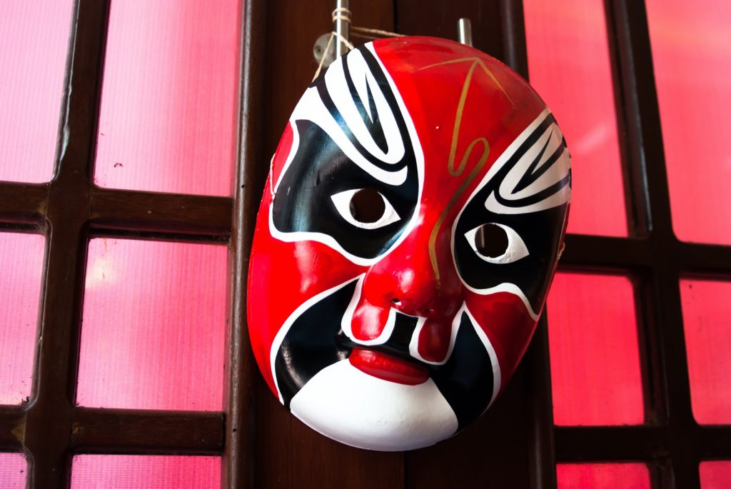 Red Chinese opera mask on colored wall