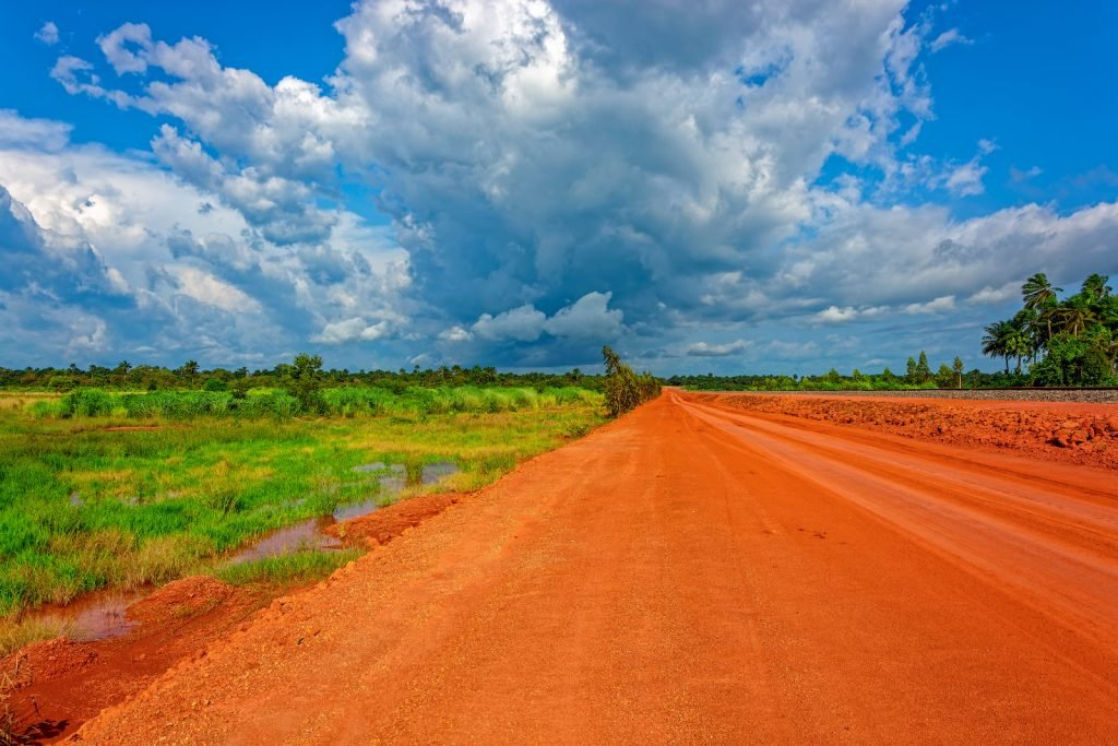 Red clay soil road in the middle of an open landscape