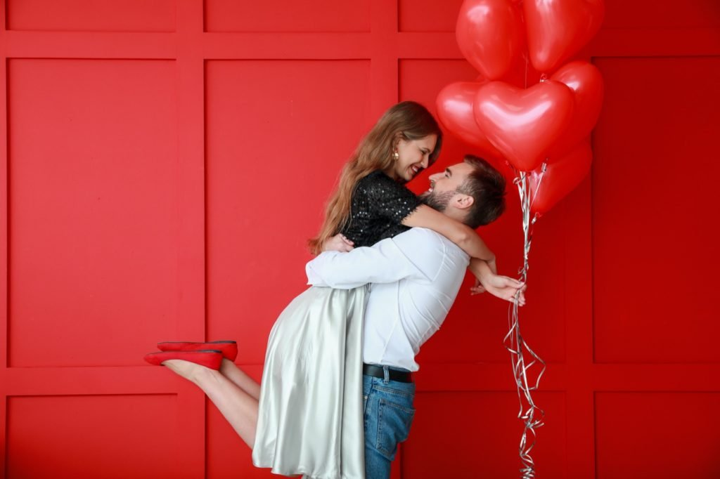 Happy couple with red heart-shaped balloons on colored background symbolizing passion and love