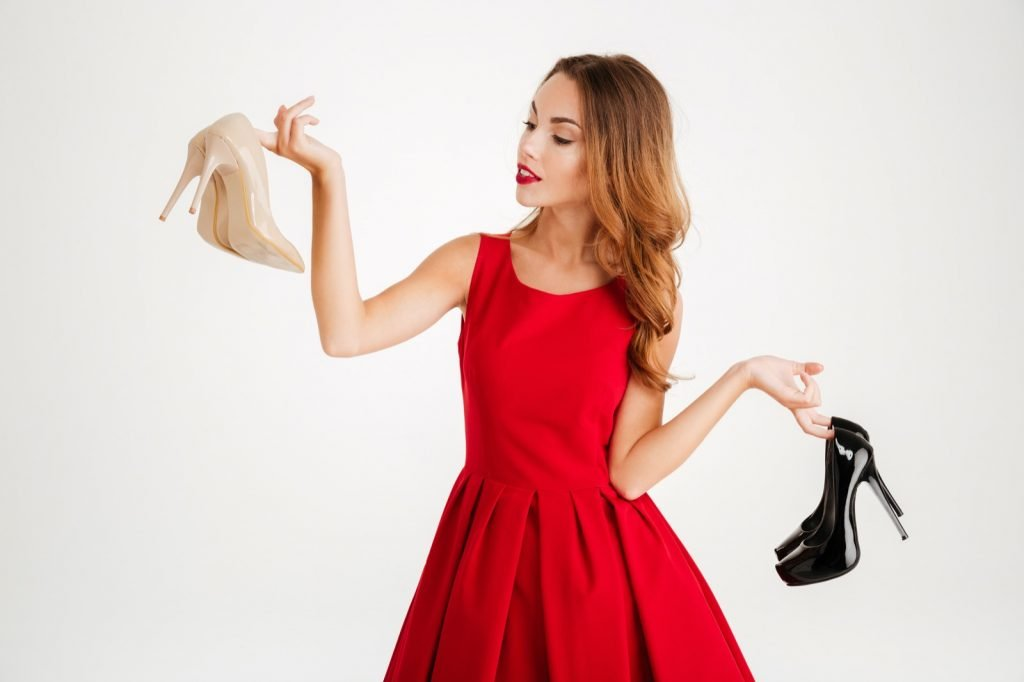 Woman holding two pairs of high heel shoes in beige and black color isolated on a white background