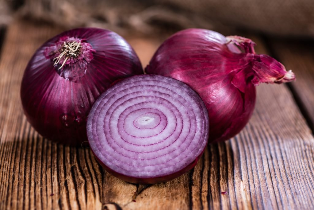 Close up of fresh red onions whole and a half on a dark wooden table