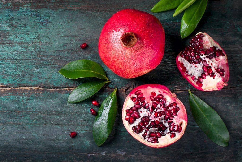 Whole and cut red pomegranate with leaves on wooden vintage background