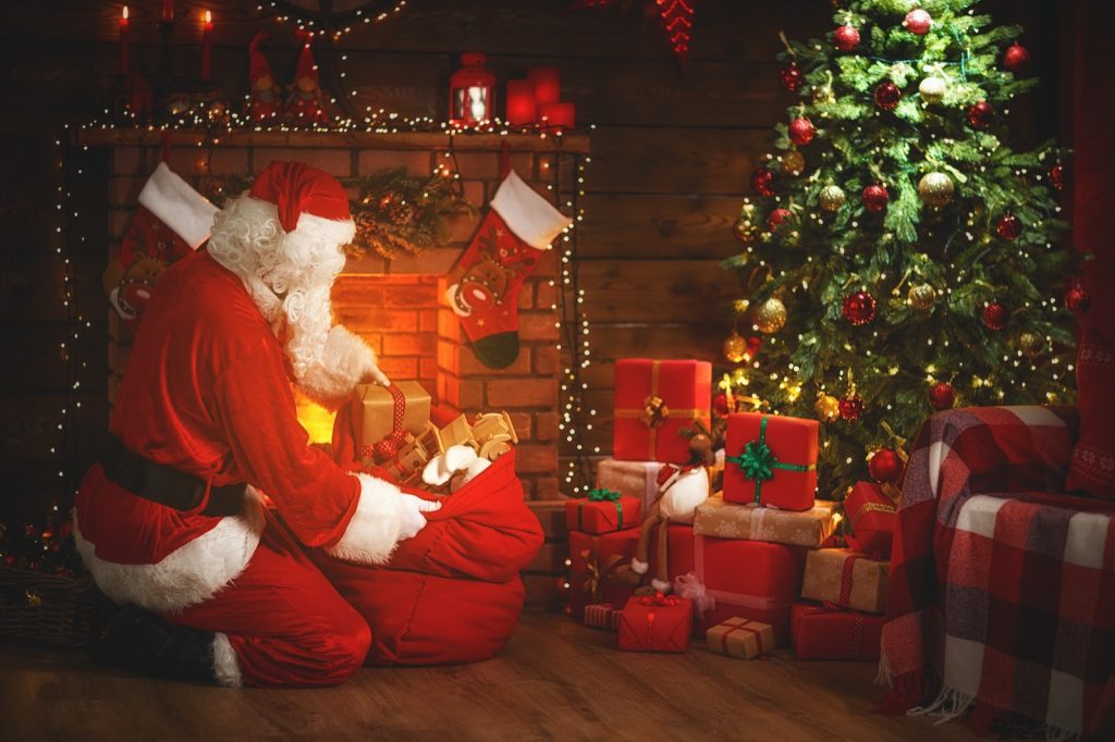 Santa Claus in red clothes near fireplace and green Christmas tree with gifts