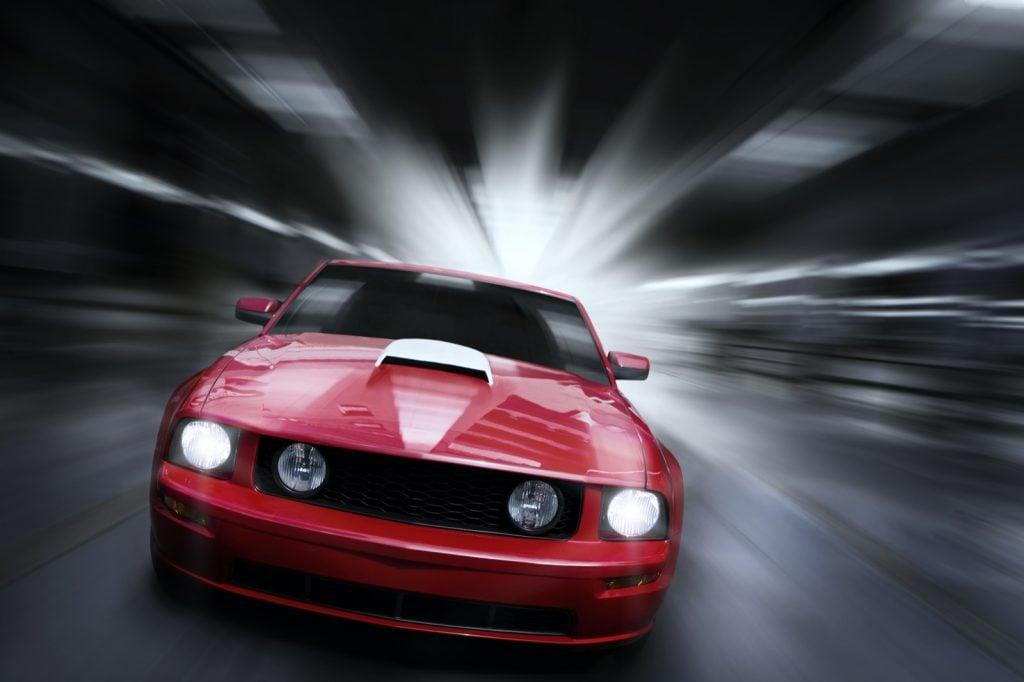 Red sport car speeding in underground tunnel