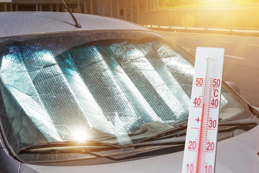 Protective reflective surface under the windshield of car keeps out heat