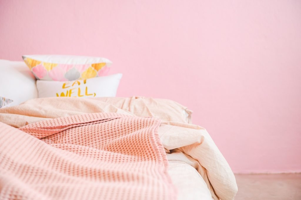 Bedroom with relaxing pink pastel walls and cozy bed and pillows