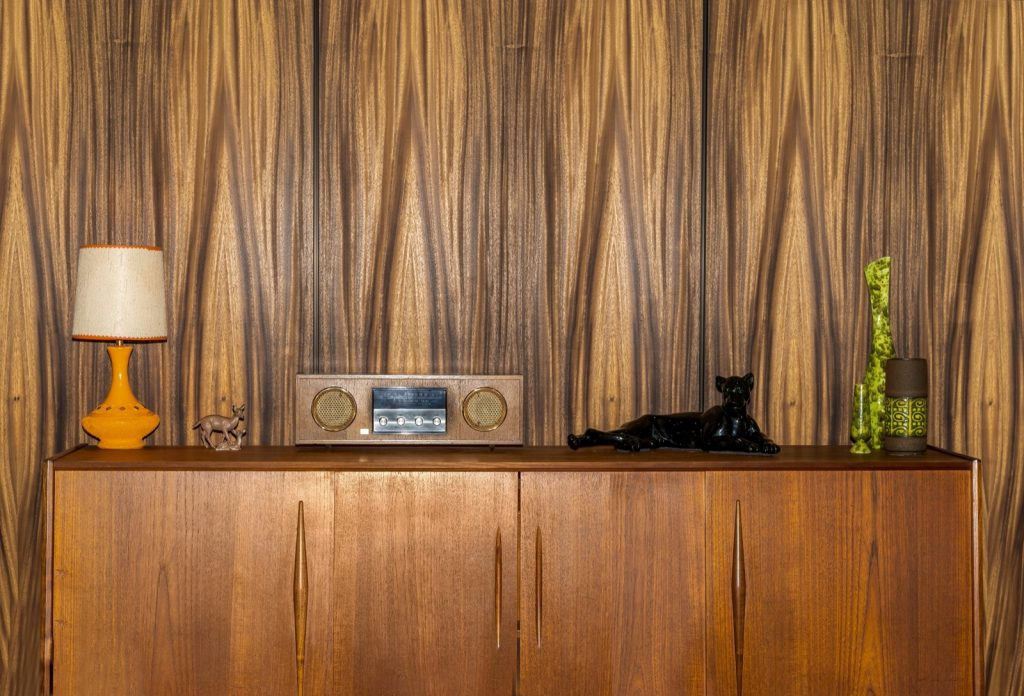 Retro 1970s teak cabinet in front of a brown wall