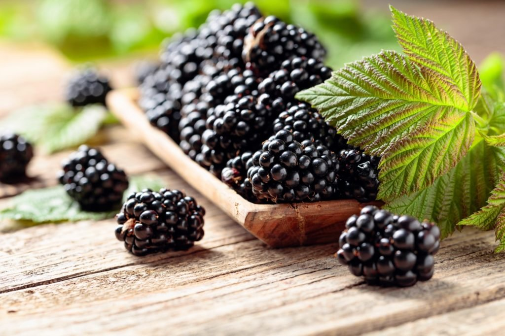 Ripe blackberries with leaves on a wooden table