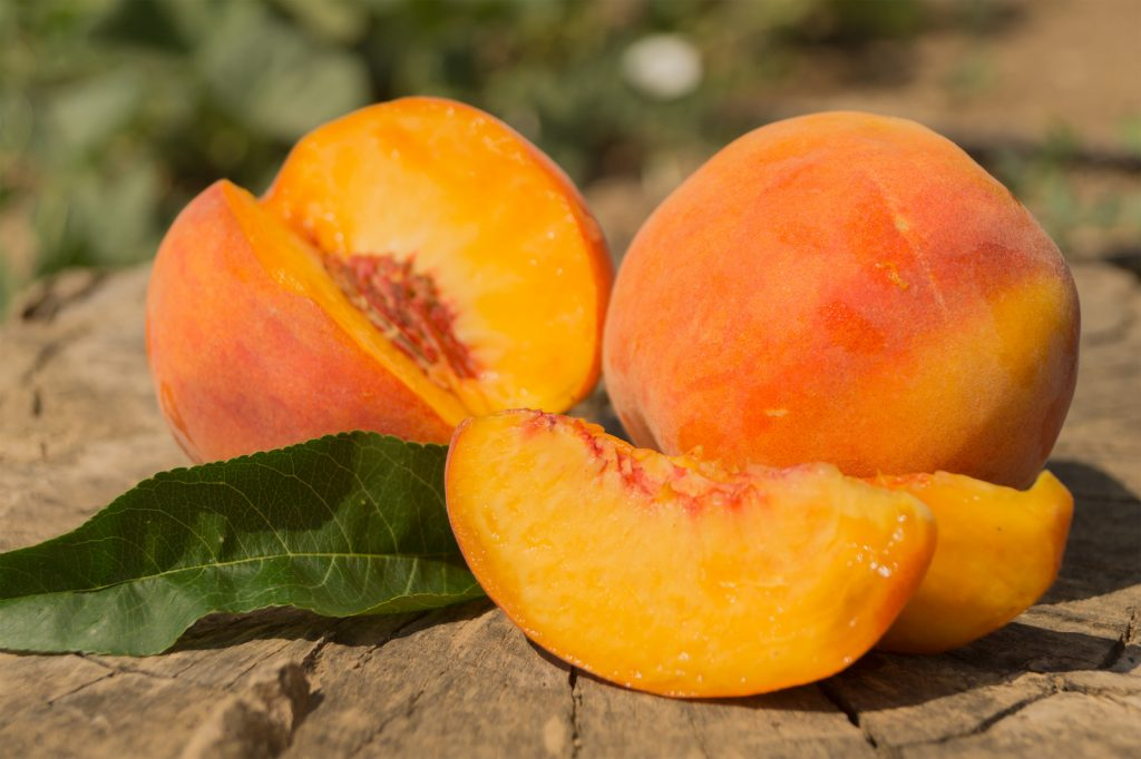 Two ripe peaches one sliced and one whole on wooden background