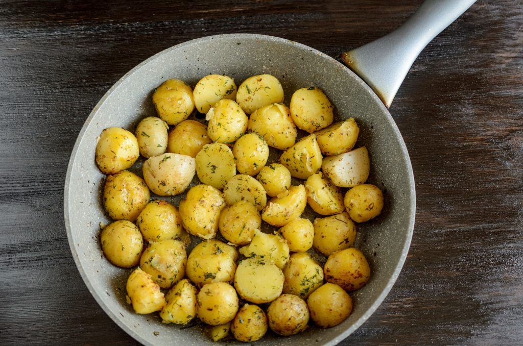 Roasted young potatoes in a pan with green herbs
