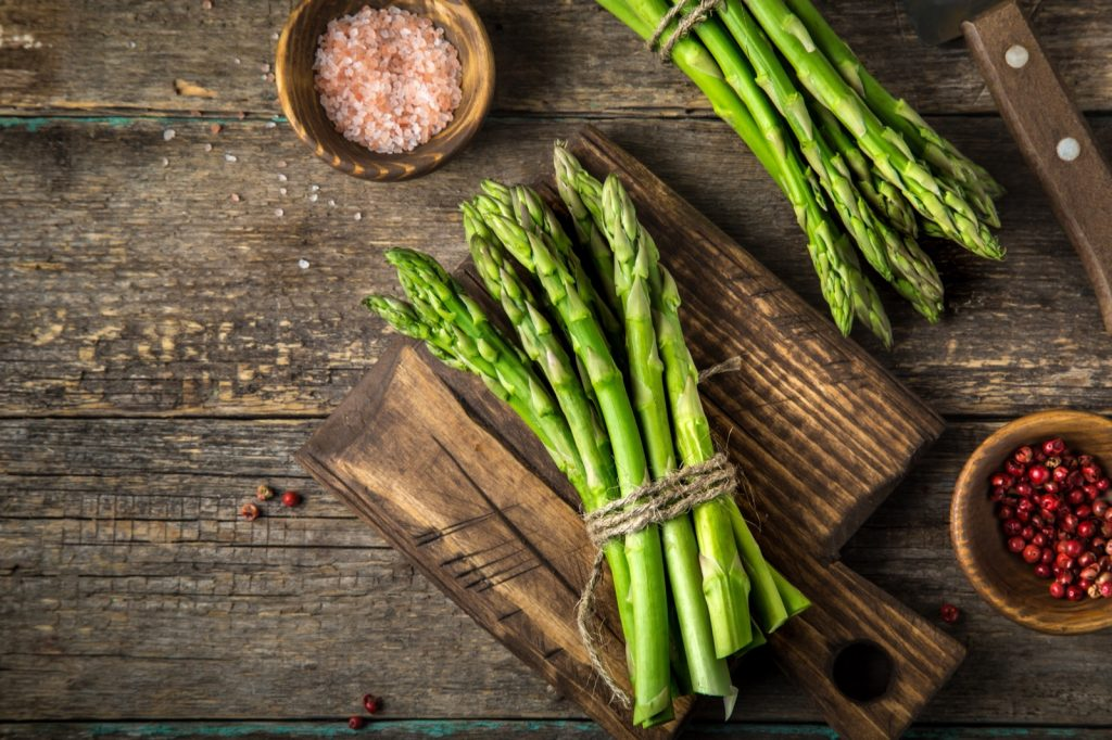 Rods of fresh green asparagus on wooden table