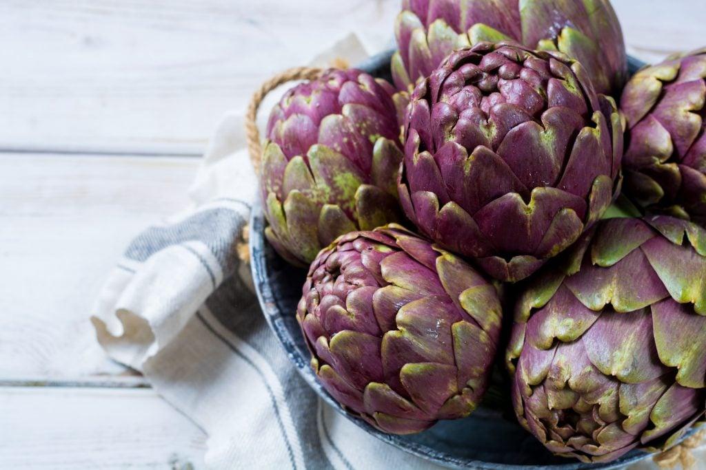 Fresh romanesco artichokes purple flower heads in a bowle
