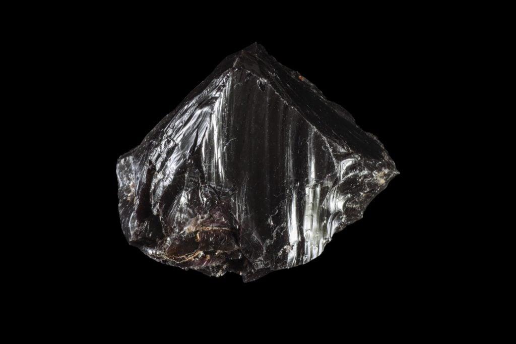Rough black jasper rock isolated on a dark background