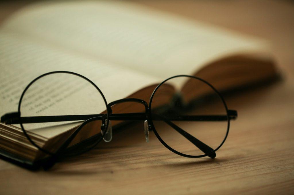 Black round glasses lying on book