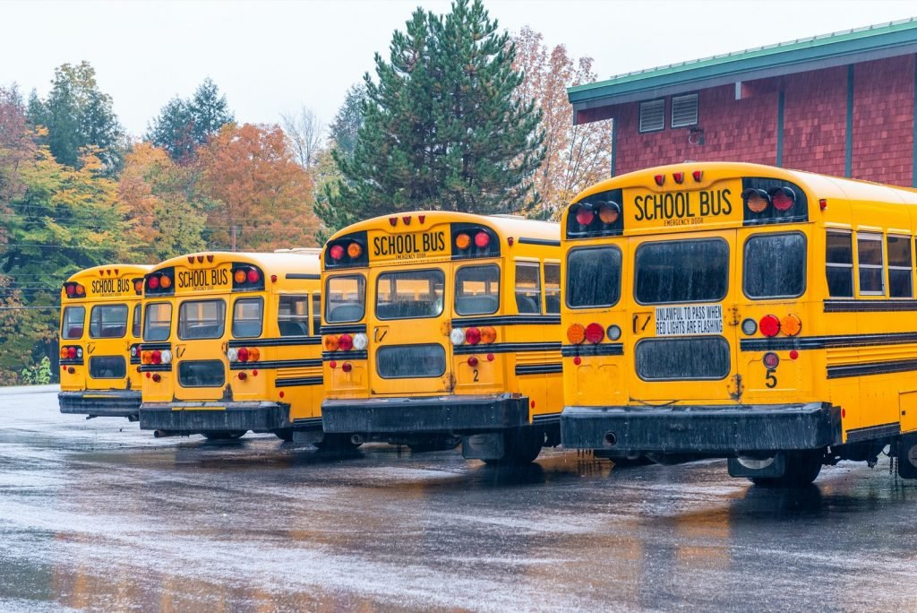 Row of yellow school buses aligned and parked