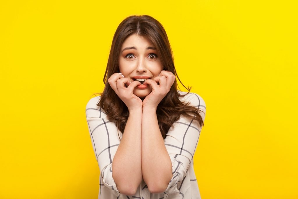 Scared cowardly brunette girl posing on a yellow background
