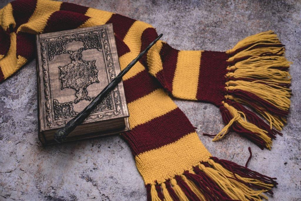 Scarf, magic wand and book of spells on gray stone background